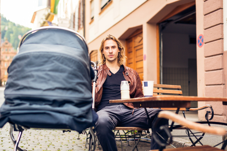 20 years old: Young Father With Baby Stroller Having Coffee At A Cafe Stock Photo