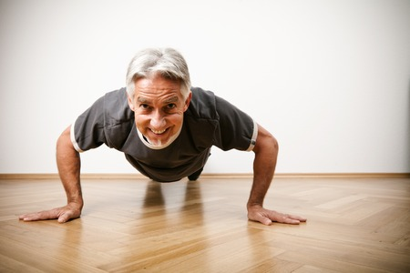 only one mid adult male: Man In His 50s Doing Pushups