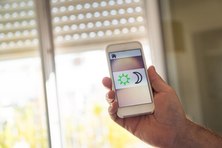 Smart Home: Man Controlling Blinds With App On His Phone