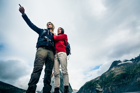 Young Couple Standing On The Mountains Peak Stock Photo