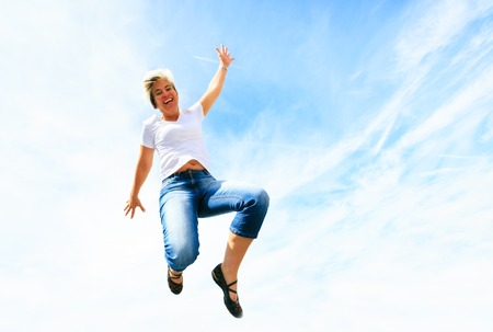 Woman In Her 50s Jumping High Into The Sky