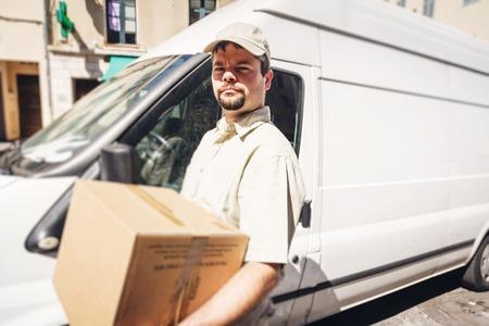 Messenger Delivering Parcel, Standing Next To His Van Banque d'images