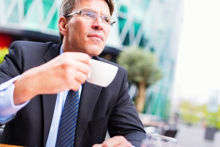 only one mid adult male: Businessman Having Coffee