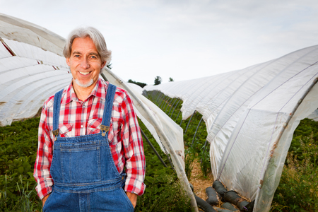 Farmer Standing In Front Of His Greenhouse
