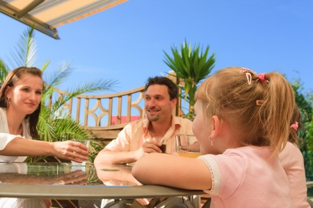 Family Having Some Drinks On The Terrace Stock Photo