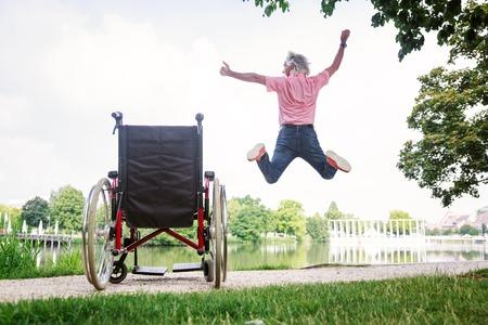 Senior Man Jumping Up From Wheelchair
