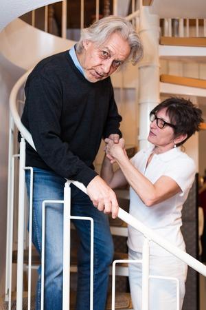 bajando escaleras: Enfermera que ayuda al hombre que sube escaleras mayores