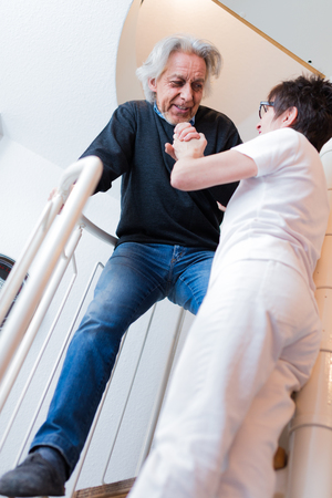 Nurse Helping Senior Man Climbing Stairs