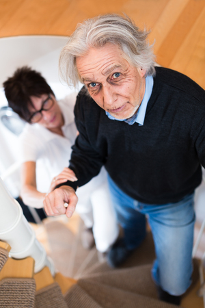 80s adult: Nurse Helping Senior Man Climbing Stairs