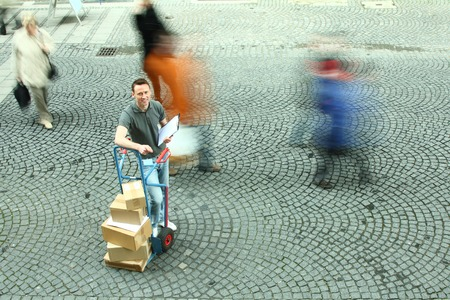 Man Standing With Dolly Of Boxes While Crowd Walks By