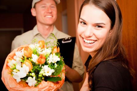 Delivery Boy Handing Over Flowers Standard-Bild
