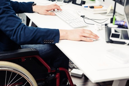 Man Sitting In Wheelchair Working In Modern Office
