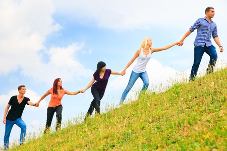 Young People Helping Each Other Climb A Hill Standard-Bild