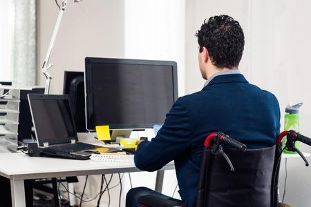 Homme assis en fauteuil roulant travaillant dans un bureau moderne Banque d'images - 72714373