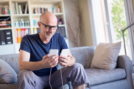 Man Transferring Data Between His Old And New Smart Phones Standard-Bild