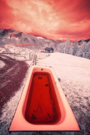 an infrared shot of a bathtub filled with rainwater, the simmental valley in the background. Stock Photo