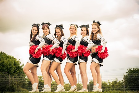 Cheerleaders Rooting For Their Team Stock Photo