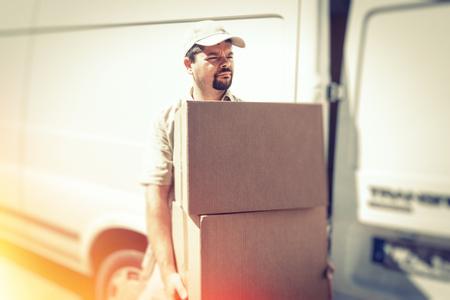 Messenger Delivering Parcel, Standing Next To His Van Reklamní fotografie