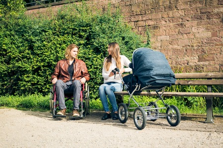 Young Parents In Wheelchair With Baby Stroller In The Park