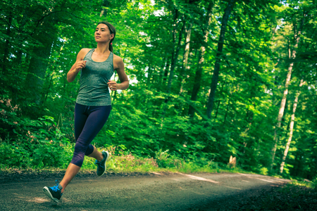 Young Woman Jogging In The Forest Stock Photo