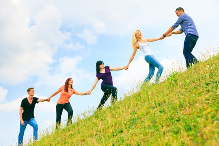 Young People Helping Each Other Climb A Hill Фото со стока