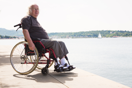 Bon vieux vieillard en fauteuil roulant en regardant la mer Banque d'images - 77879382