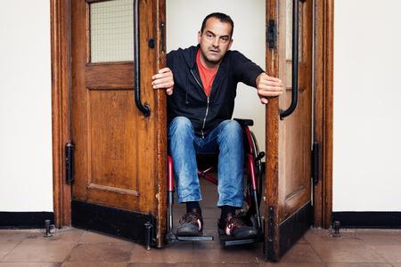 Homme en fauteuil roulant passe par la porte Banque d'images - 79972146