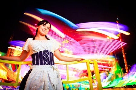tracht: Young Woman Sitting Next To Carousel Stock Photo