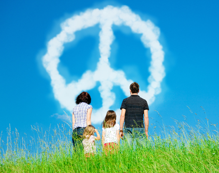 Family Looking At Clouds Forming A Peace Symbol Stock Photo
