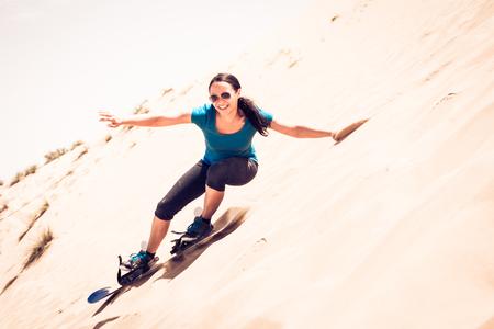 Tourist Sandboarding In The Desert Zdjęcie Seryjne - 83299050