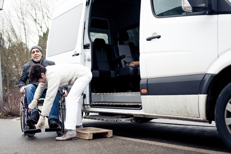 Nurse Helping Senior Man Exit A Van Stock Photo