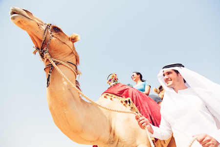 non: Arabian Man And Tourist Riding A Camel