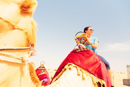A female tourist is riding a camel in Dubai, UAE. Stock Photo