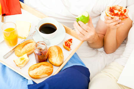 A young couple is having breakfast in bed