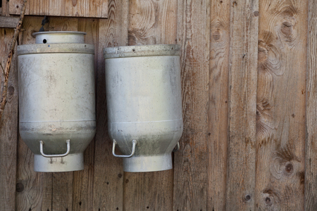 milk canisters on a wooden wall