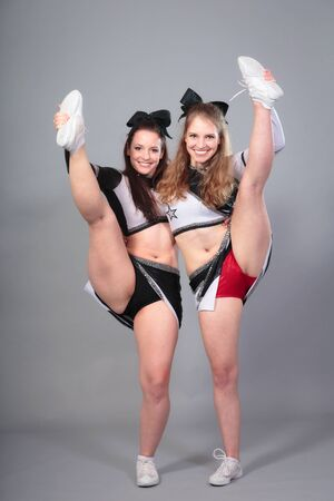 Two Cheerleaders Performing A Stretch Stock Photo