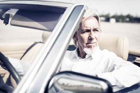 Senior Man Driving A Convertible Classic Car
