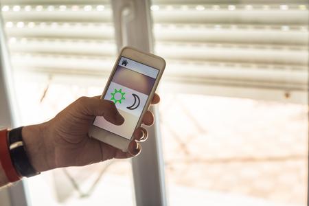 Smart Home: Un homme contrôlant les stores avec son téléphone