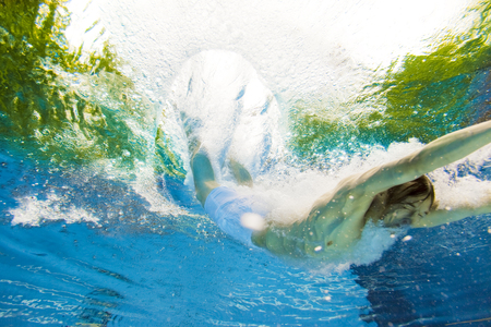 Underwater View Of A Man Jumping Into The Water