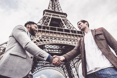 Two Men Shaking Hands By The Eiffel Tower