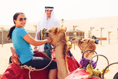 Arabian Man And Tourist Riding A Camel