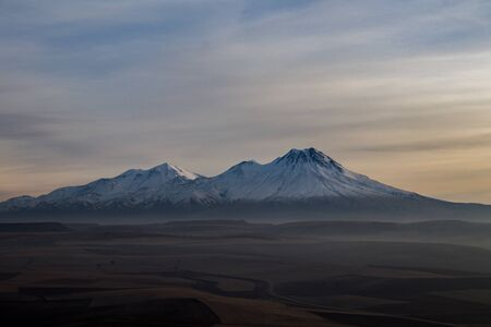 Snowy Mount Hasan. Volcano in Aksaray Turkey, Anatolia. Sunset. Pink Red Orange sky