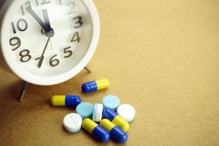 medicine background: pills and alarm clock