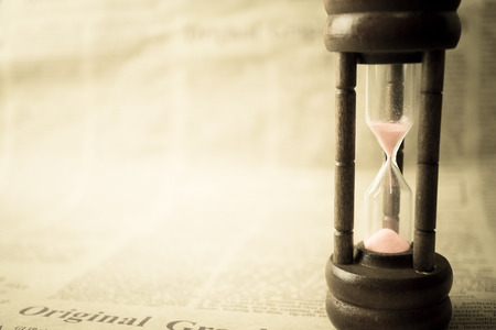 old time: hourglass on newspaper in vintage style Stock Photo