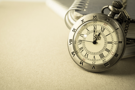 past midnight: vintage pocket watch and the book on craft paper Stock Photo
