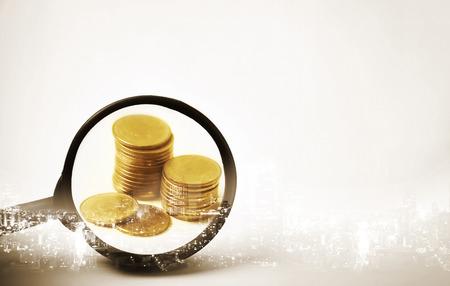 市内の金融と銀行の概念のためのコインの行で虫眼鏡の焦点の二重露光