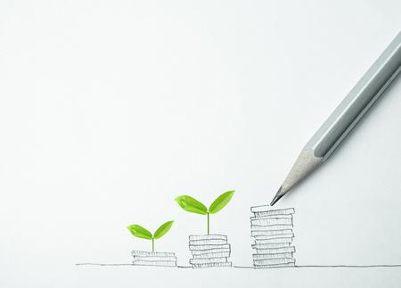 お金の概念のための鉛筆とコイン金図面の行で植物の成長 写真素材