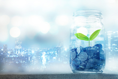 Double exposure of Growing plant on coin money in the bottle for money concept