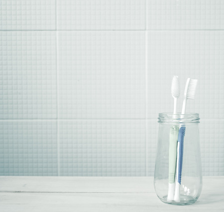 toothbrush in the glass bottle in bathroom soft color for health care concept