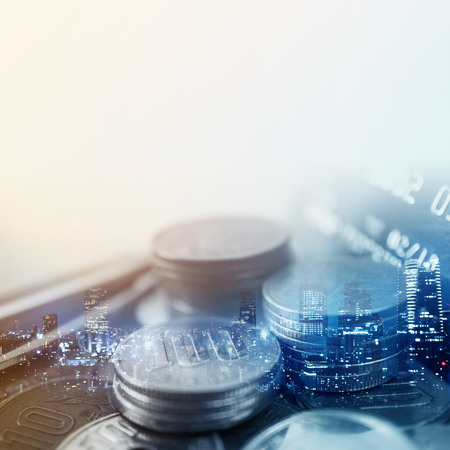 banking concept: Double exposure of city and rows of coins for finance and banking concept